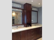 Custom vanity with linen tower and quartz countertop. Mirror frames were stained to match and