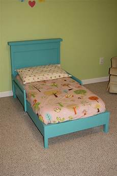 white traditional toddler bed with rustic headboard