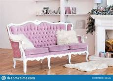 pink velvet sofa with buttons and fluffy pillows stock