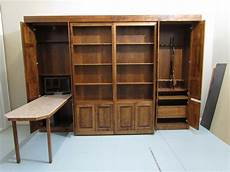library style murphy bed with gun cabinet and