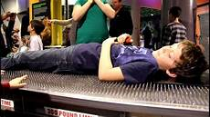 jackson lays on a bed of nails discovery place