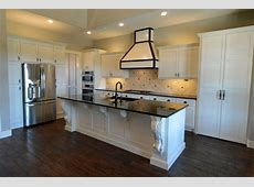 Open kitchen plan with large island, custom white cabinets, large decorative corbels, beveled