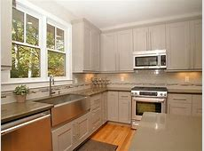 This modern kitchen features a farm sink, stainless steel appliances, quartz countertops and