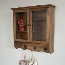 wooden glazed wall cabinet with shelves and hooks melody