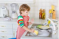 clothes for boys dishes blond kid boy washing dishes in domestic kitchen
