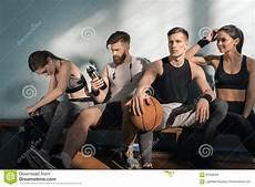 uomini sportivi uomini sportivi e donne che si siedono sul banco in