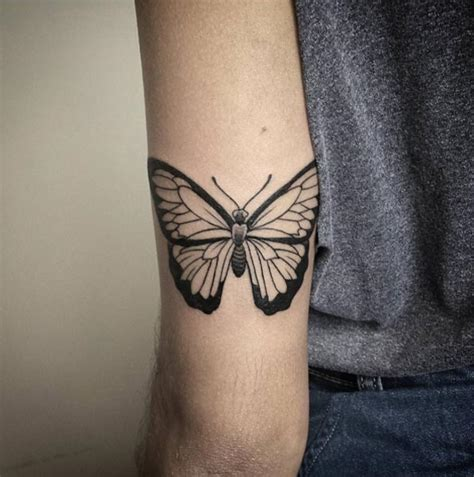 black butterfly tattoo on elbow