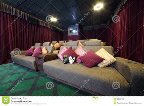 Two Masks On Couch With Cushions And Projector Stock Photo