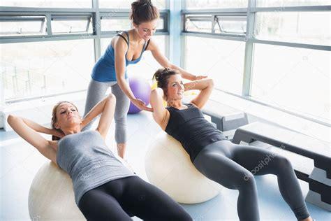 mujres asiedo mujeres haciendo sentadillas en pelotas de ejercicio en el