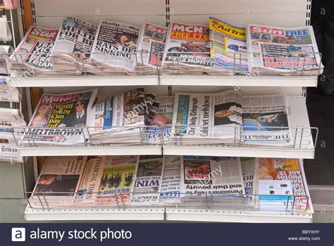 newspapers on a shelf for sale in a uk newsagents