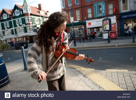 a man busking in the street playing the violin in the