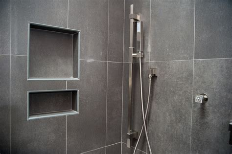 Chrome corner head shower with built in shower niche for soap storage and dark ceramic wall tile