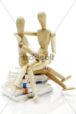 jointed doll ebook two wooden jointed figures sitting on a pile of banknotes