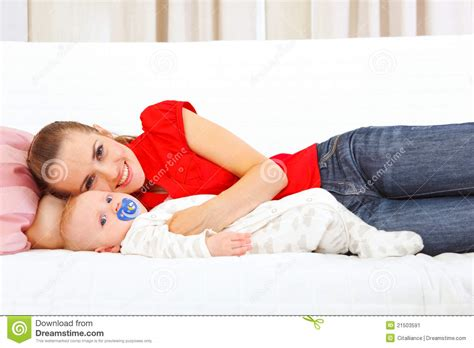 laying on couch smiling mother and baby laying on couch stock image