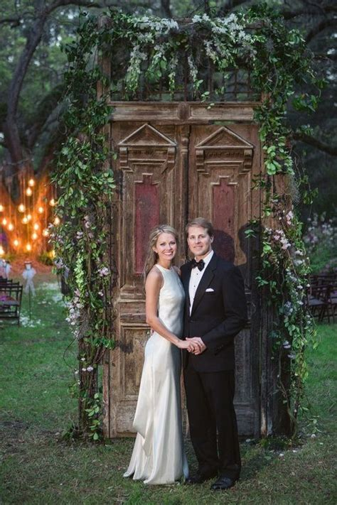 cameran eubanks and dr jason wimberly in front of rustic doors decorated with greenery http