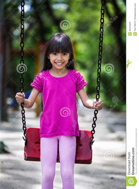 swinging in asia happy asian little girl smiling on swing stock photos