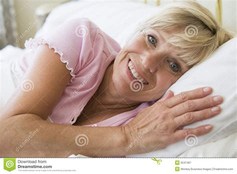 girl lying bed with flowers woman lying in bed smiling royalty free stock photography