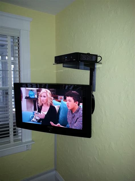 swing tv tv on wall with swing arm mount and an a v shelf above for