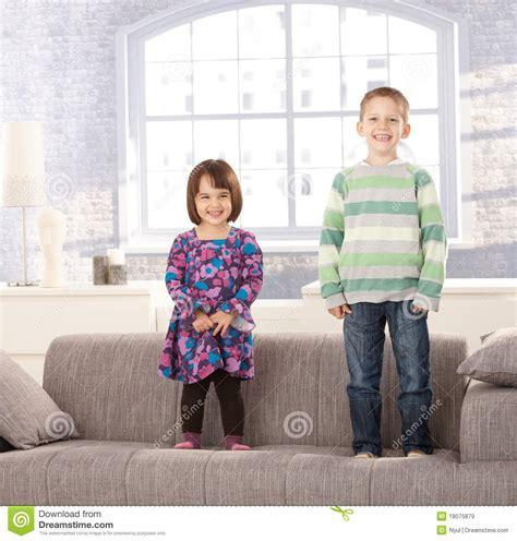 kids on couch laughing kids standing on couch royalty free stock images