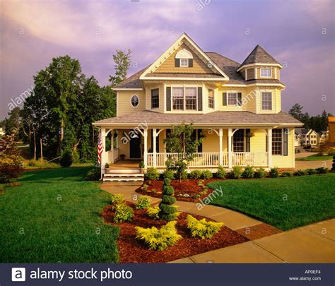 yellow victorian house large two story yellow victorian house with blue shutters and a large stock photo