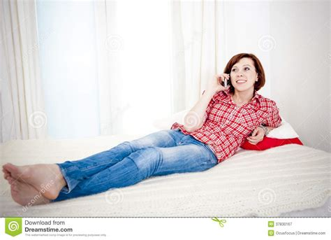 lying down on the couch red haired woman lying down on couch talking on mobile