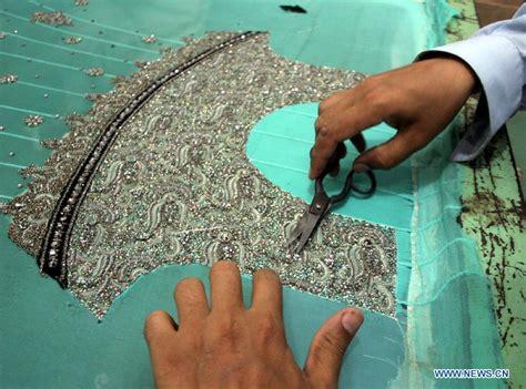 handmade lwork workers work on handmade suit before eid ul fitr