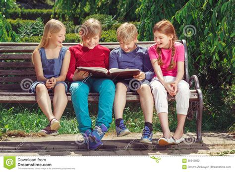kids reading bench nice smiling children sitting on the bench stock photo