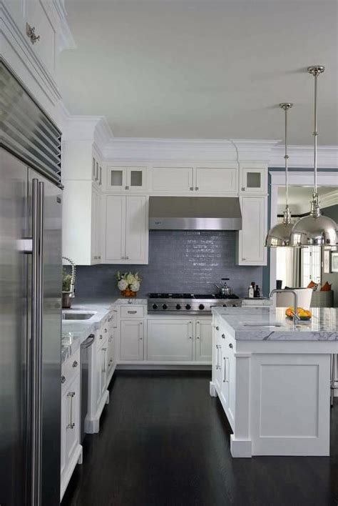white and blue kitchen features white shaker cabinets paired with gray marble countertops and a