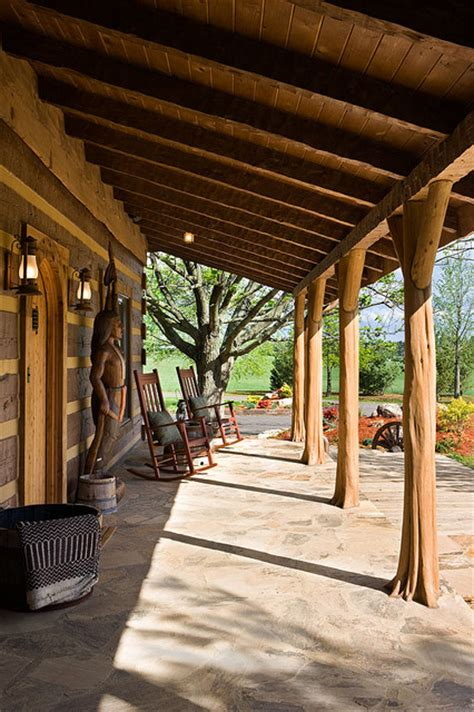 veranda western style log home with barn wood and western decor traditional