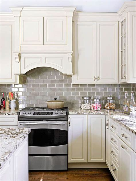 grey tile backsplash smoke gray glass subway tile backsplash white shaker cabinets neutral quartz countertop