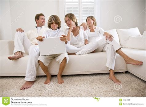 white couch with kids boy using laptop sitting with family on white sofa stock