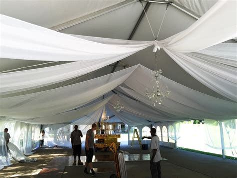 step by step ceiling draping wedding tent with chandeliers and sheer draping in illinois