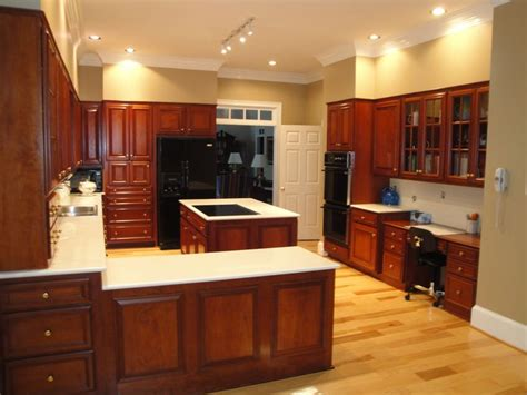 Does Flooring Go Cabinets by Hickory Floors Cherry Cabinets Black Appliances Counter