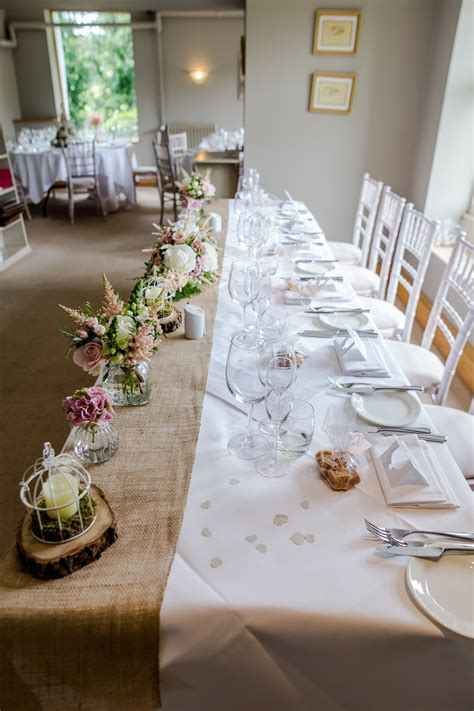 top table design wedding hessian runners bird cages log slices bottles moss and flowers