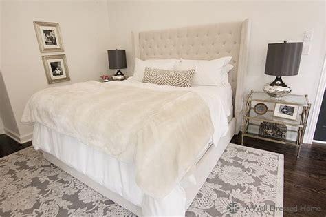 stunning bedroom  beige tufted headboard accented  soft white bedding zebra lumbar
