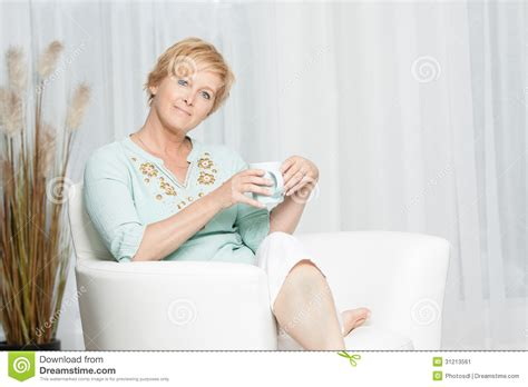 having on couch woman having coffee while relaxing at home stock image
