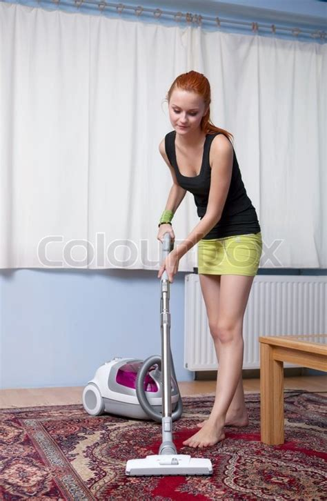 New Home Floor Plans And Prices by Young Woman With Vacuum Cleaner At Home Stock Photo