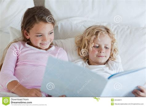 brother and sister in bed brother and sister reading bed time story stock image
