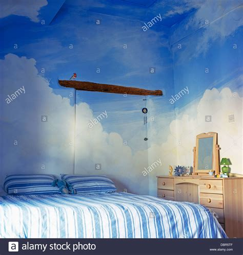 soft sky blue walls float above the white cabinetry and marble trompe l oeil blue sky and clouds painted on walls and