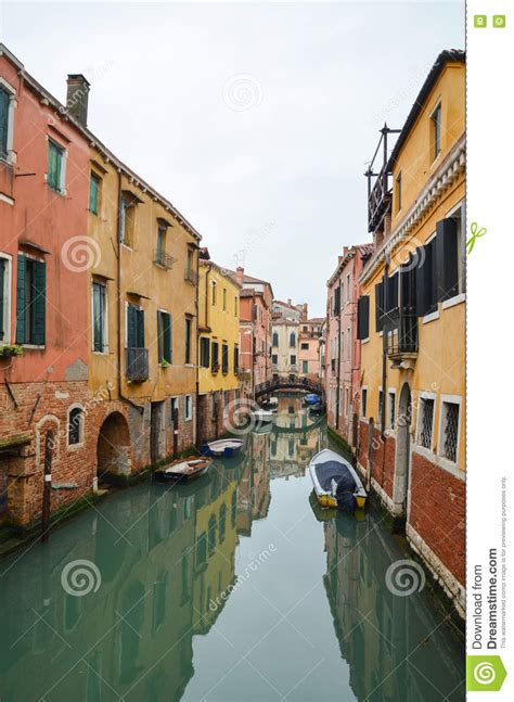 narrow canal among old houses in venice italy stock - Old Boatyard Venice