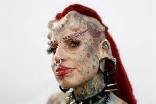 impressive tattoos and piercings decorate faces at a