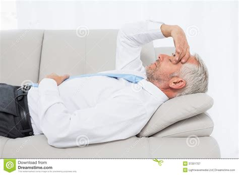 mature couch tired mature businessman resting on sofa in living room