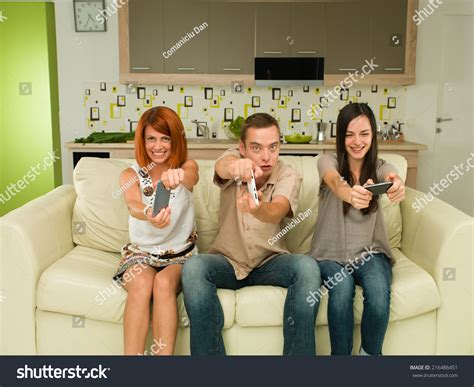 people having on a couch three young happy caucasian people sitting on couch