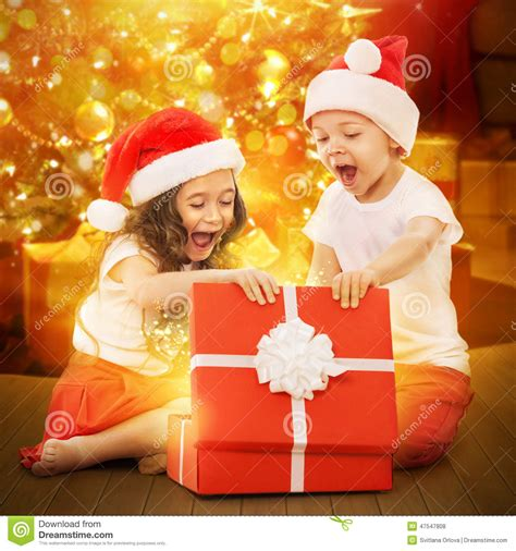 happy kids in santa hat opening a gift box stock photo