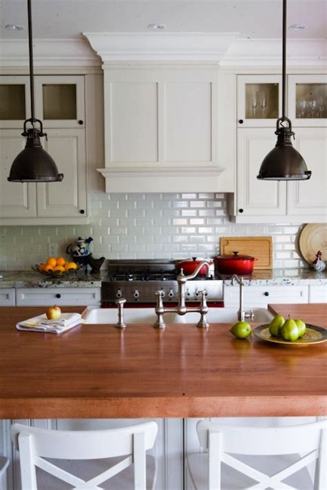 kitchen with white cabinets backsplash and bronze accents rubbed bronze pendants design ideas