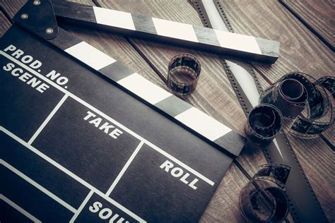 www film film movie clapper and film reel on a wooden background