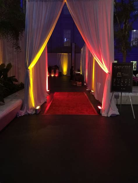 Pipe and drape entrance with uplighting and red carpet for