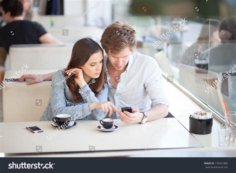 For Couples On Phone Surfing The Web Looking At Photos On Mobile