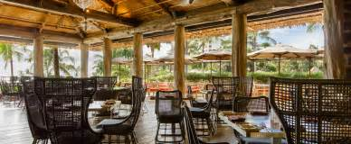 Tables on a covered patio with rustic log pillars and umbrellaed
