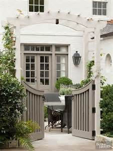 curved garden gate with arbor and hedge painted white